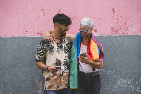 Gay couple in front of pink and grey wall - JCMF00723