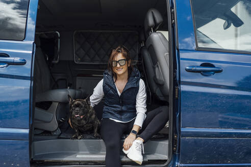 Portrait of smiling woman sitting with her bulldog in van - OCMF01207