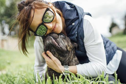 Portrait of happy woman cuddling her bulldog on a meadow - OCMF01213