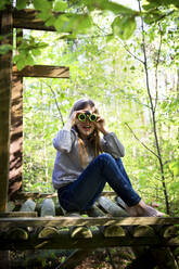 Portrait of girl using binoculars in forest - LVF08874