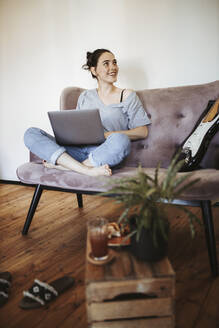 Portrait of smiling young woman sitting on couch at home with laptop - DAWF01457