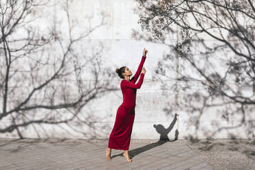 Woman in red dress with dancer pose and tree shadows on  wall - TCEF00623
