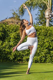 Woman doing yoga on lawn in sunshine - DLTSF00657