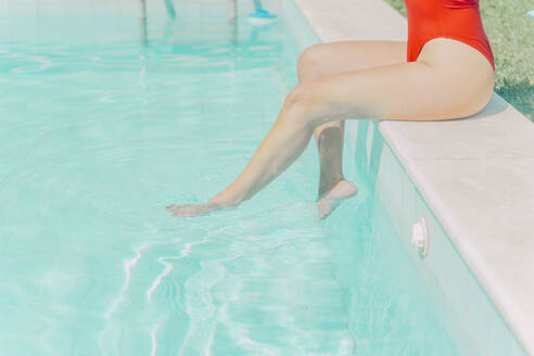 Legs of woman wearing red swimsuit sitting at the poolside - ERRF03659