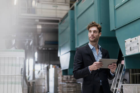 Young businessman holding tablet in a factory - DIGF10678