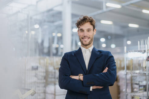 Portrait of a smiling young businessman in a factory - DIGF10699