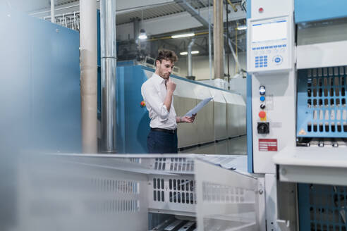 Young businessman holding papers in a factory - DIGF10759
