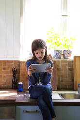 Girl sitting on sink in the kitchen looking at digital tablet - LVF08877