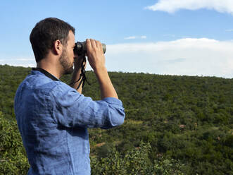 Man looking out for animals with binoculars, South Africa - VEGF02161