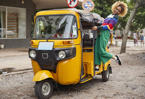 Cheerful young woman standing on rickshaw in city - VEGF02166
