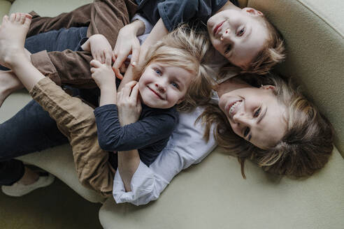 High angle view of happy mother lying with sons on sofa in living room at home - OGF00399