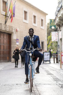 Portrait of young businessman riding bicycle in the city - EGAF00077