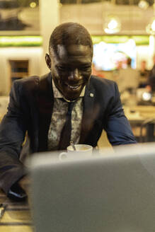 Smiling young businessman working on laptop in a coffee shop - EGAF00086