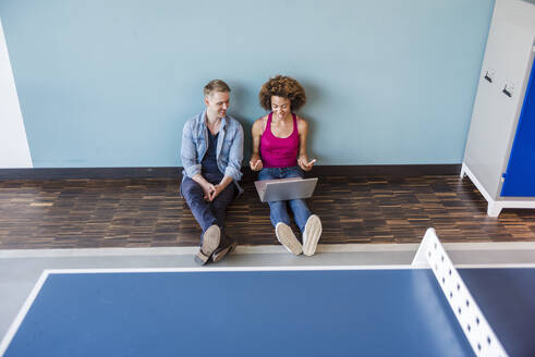 Young woman and man sitting on floor in modern office, using laptop - DIGF10857