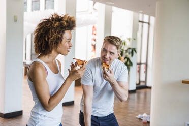 Young business people sharing pizza for lunch in a modern office with ping pong table - DIGF10866