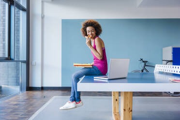 Young woman sitting on ping pong table, eating pizza, using laptop - DIGF10875