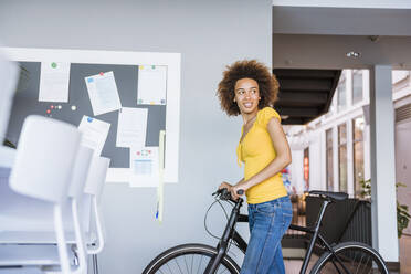 Young woman pushing bycicle in office - DIGF10878