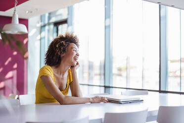 Young woman working in modern office, laughing - DIGF10881