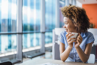 Young woman sitting in modern office, drinking coffee - DIGF10896
