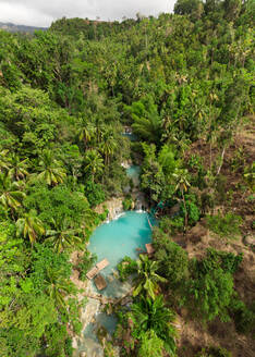 Aerial view of the famous Cambugahay Falls on Siquijor, Philippines. With rafts on the turquoise water in the middle of lush forest. - AAEF08422