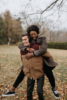 A white man giving a black woman a piggy back on a leaf strewn lawn and laughing. - ISF24039