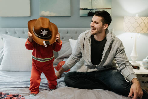 A father sitting on a bed with his childtrying on a cowboy hat. - ISF24081