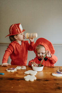 Two children dressed as firefighters at a table decorating  cookies with chocolates and sprinkles. - ISF24084
