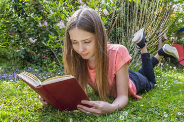 Girl lying on meadow reading a book - SARF04567
