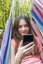 Portrait of smiling girl in hammock looking at cell phone - SARF04576