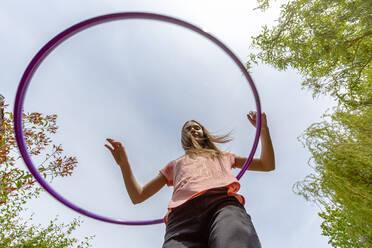 Girl with hula hoop in garden - SARF04579