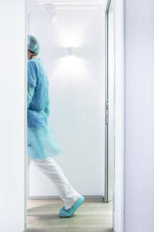 Mature male dentist walking in illuminated hallway - JCMF00728