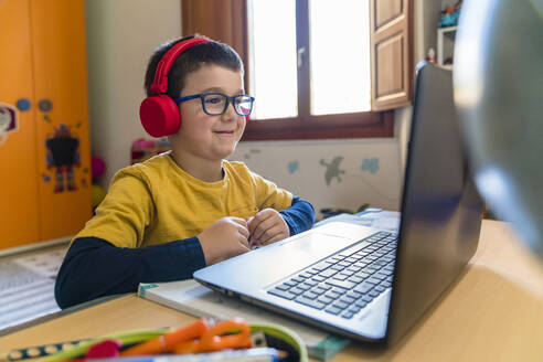 Smiling male student listening through headphones while looking at laptop during homeschooling - MGIF00951