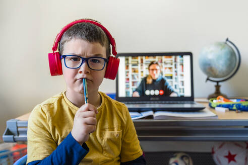 Thoughtful boy sitting against laptop during video call at home - MGIF00954