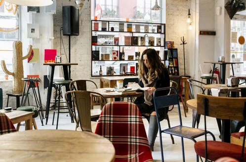 Woman reading a book in coffee shop - MGOF04247