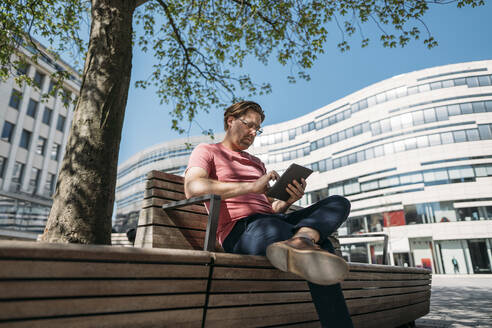 Freelancer sitting on a bench in the city using tablet - JOSEF00548