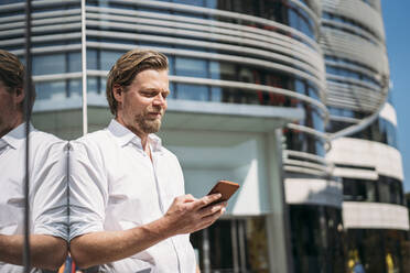 Businessman in the city leaning against glass front checking smartphone - JOSEF00572