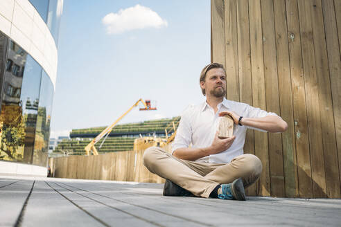 Businessman sitting on the ground at construction site holding wooden house model - JOSEF00587