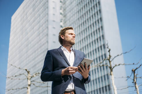 Businessman holding tablet in the city - JOSEF00590