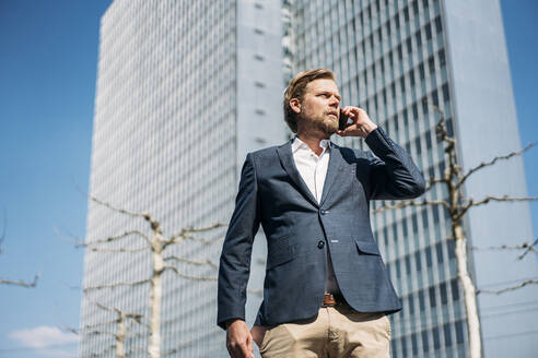Portrait of businessman on the phone in the city - JOSEF00593