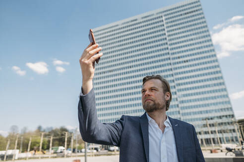 Businessman using smartphone in the city - JOSEF00605