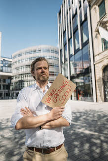 Shopkeeper holding cardboard with opening announcement in the city - JOSEF00623