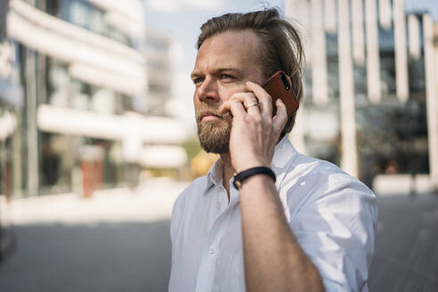 Portrait of businessman on the phone in the city - JOSEF00626