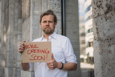 Shopkeeper holding cardboard with opening announcement in the city - JOSEF00632