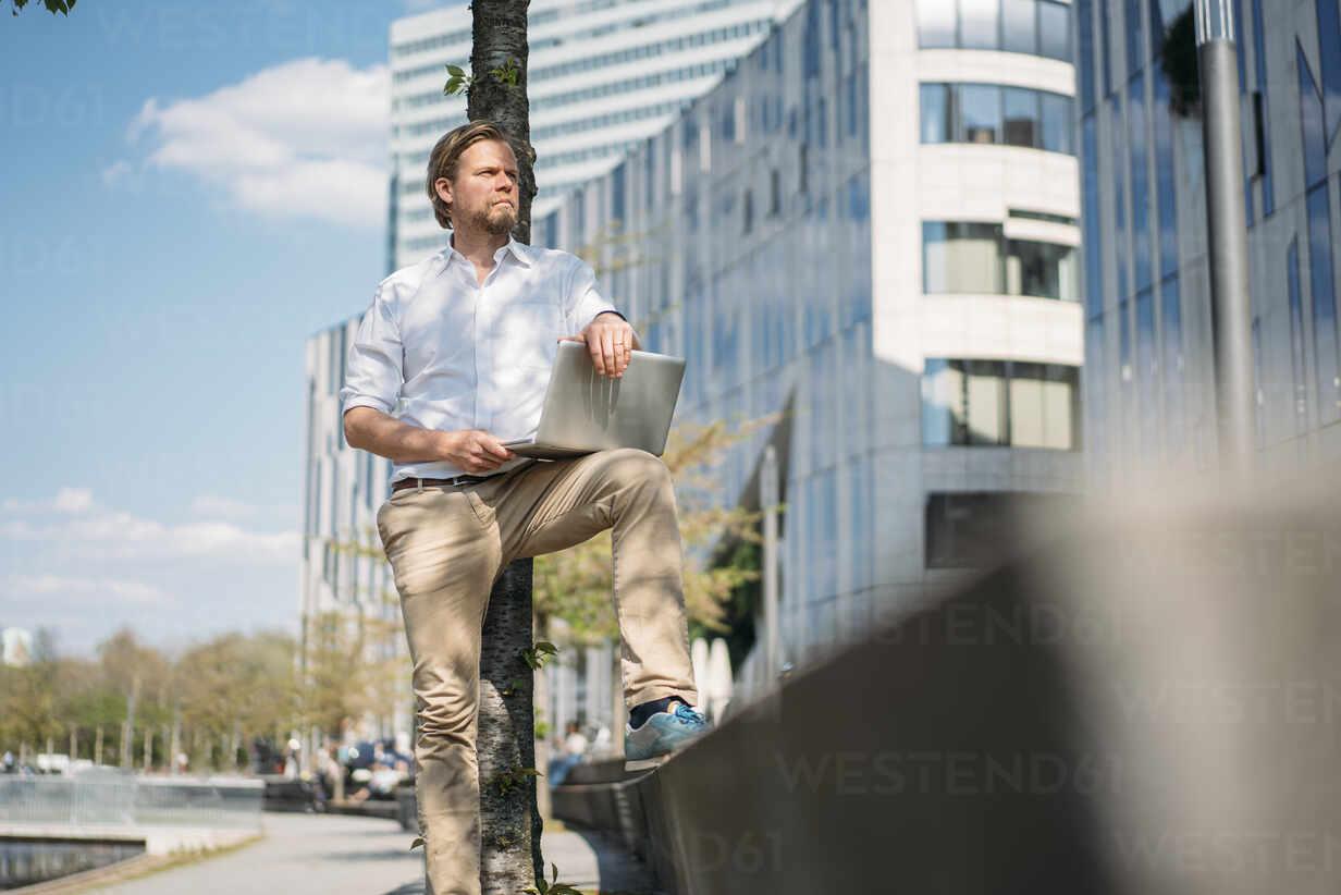 Businessman using laptop in the city - JOSEF00644 - Joseffson/Westend61