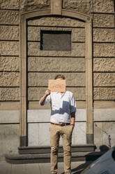 Shopkeeper holding cardboard with closed announcement in the city - JOSEF00647
