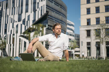Businessman with laptop sitting in grass in the city - JOSEF00653