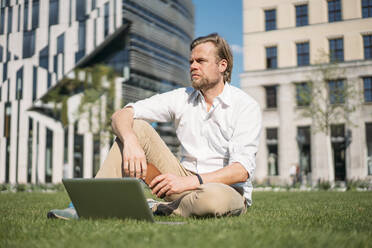 Businessman with laptop sitting in grass in the city - JOSEF00656