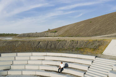 Male professional sitting at amphitheater steps against sky on sunny day - MOEF02874