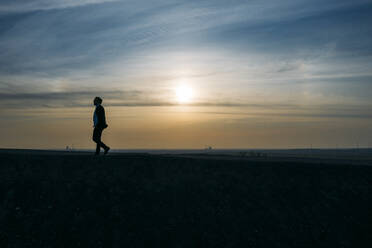 Silhouette businessman walking on hill against sky during sunset - MOEF02883