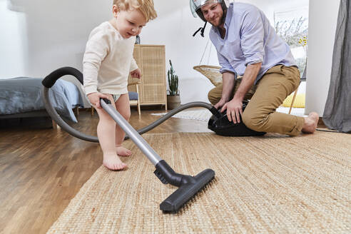 Man looking at cute toddler son cleaning carpet with vacuum cleaner in living room at home - FSF01072